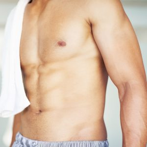 Cropped image of a muscular man with a towel on the shoulder